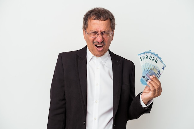 Middle aged indian business man holding bills isolated on white background screaming very angry and aggressive.