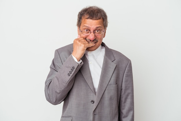 Middle aged indian business man isolated on white background biting fingernails, nervous and very anxious.
