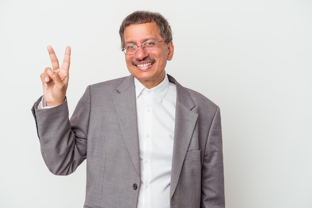 Middle aged indian business man isolated on white background joyful and carefree showing a peace symbol with fingers.