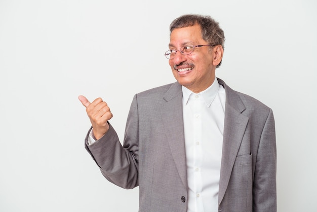 Middle aged indian business man isolated on white background points with thumb finger away, laughing and carefree.
