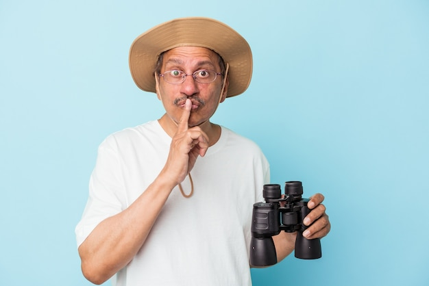 Middle aged indian fisherman holding rod isolated on blue background keeping a secret or asking for silence.