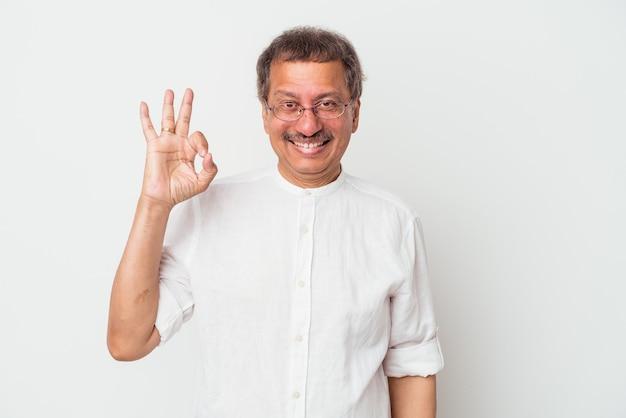 白い背景で隔離された中年のインド人は、陽気で自信を持って大丈夫なジェスチャーを示しています。