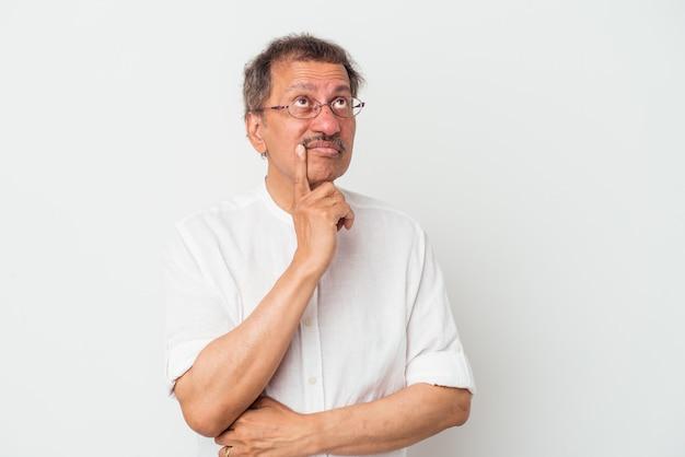 考え、戦略を計画し、ビジネスの方法を考えて、白い背景に孤立した中年のインド人。