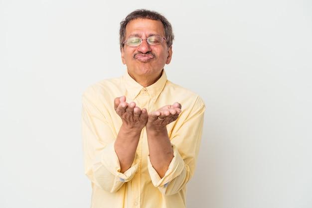 中年のインド人男性は、白い背景で唇を折り、手のひらを持って空気のキスを送信します。