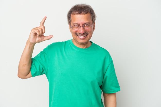 中年のインド人男性は、白い背景に孤立し、人差し指で少し何かを持って、笑顔で自信を持っています。