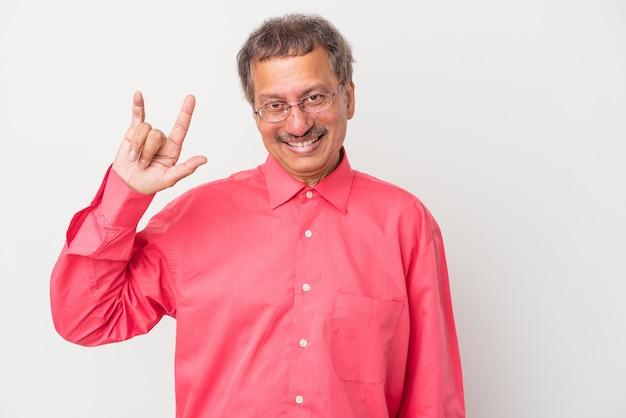 革命の概念として角のジェスチャーを示す白い背景に分離された中年のインド人。