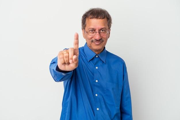 흰색 배경에 격리된 중년 인도 남자는 손가락으로 1번을 보여줍니다.