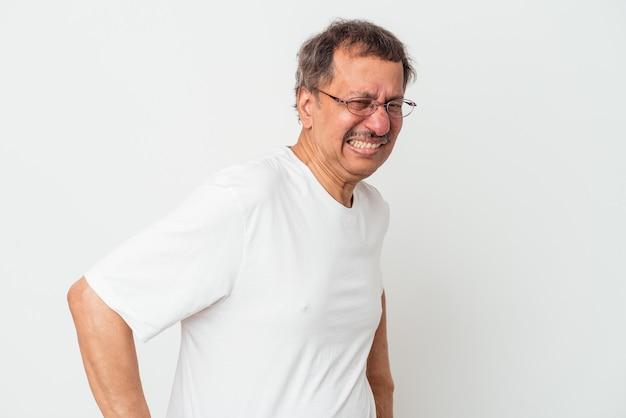 背中の痛みに苦しんでいる白い背景で隔離される中年のインド人男性。