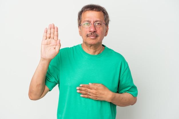 誓いを立て、胸に手を置いて、白い背景で隔離された中年のインド人男性。