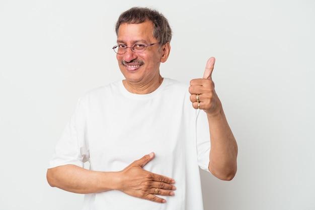 白い背景で隔離される中年のインド人はおなかに触れ、優しく微笑んで、食事と満足の概念。