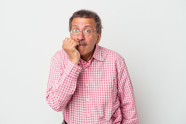 Middle aged indian man isolated on white background biting fingernails, nervous and very anxious.