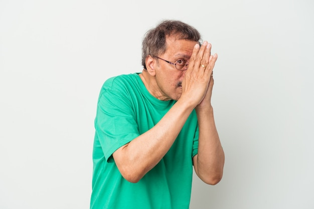 Middle aged indian man isolated on white background blink through fingers frightened and nervous.