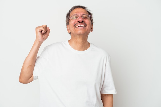 Middle aged indian man isolated on white background celebrating a victory, passion and enthusiasm, happy expression.
