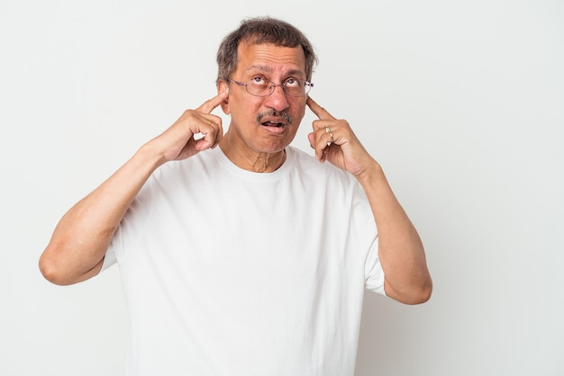 Middle aged indian man isolated on white background covering ears with fingers, stressed and desperate by a loudly ambient.