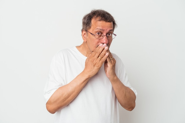 Middle aged indian man isolated on white background covering mouth with hands looking worried.