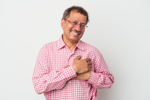 Middle aged indian man isolated on white background has friendly expression, pressing palm to chest. love concept.