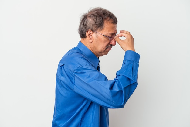 Middle aged indian man isolated on white background having a head ache, touching front of the face.