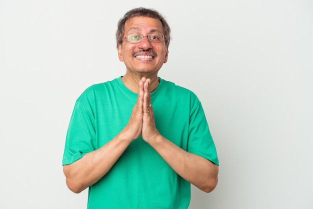 Middle aged indian man isolated on white background holding hands in pray near mouth, feels confident.
