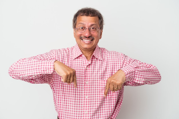 Middle aged indian man isolated on white background points down with fingers, positive feeling.
