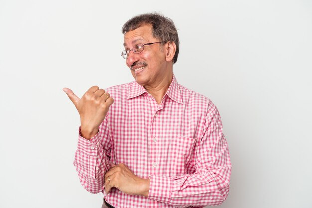 Middle aged indian man isolated on white background points with thumb finger away, laughing and carefree.