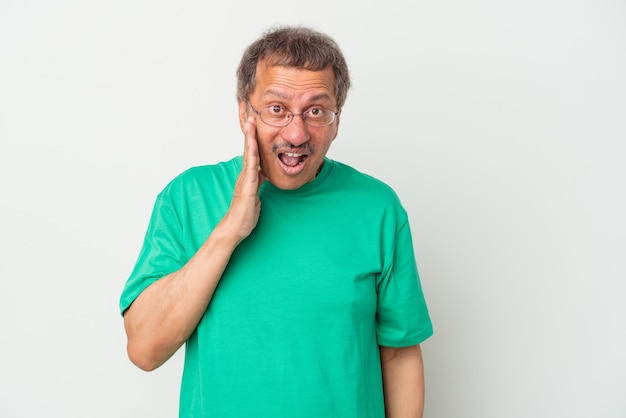 Middle aged indian man isolated on white background shouts loud, keeps eyes opened and hands tense.