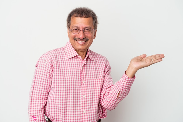 Middle aged indian man isolated on white background showing a copy space on a palm and holding another hand on waist.