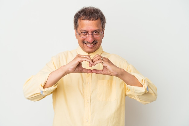Middle aged indian man isolated on white background smiling and showing a heart shape with hands.