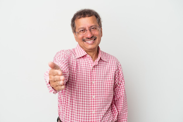 Middle aged indian man isolated on white background stretching hand at camera in greeting gesture.