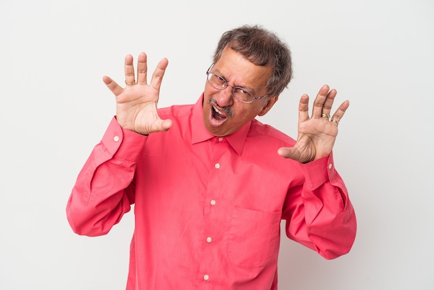 Middle aged indian man isolated on white background upset screaming with tense hands.