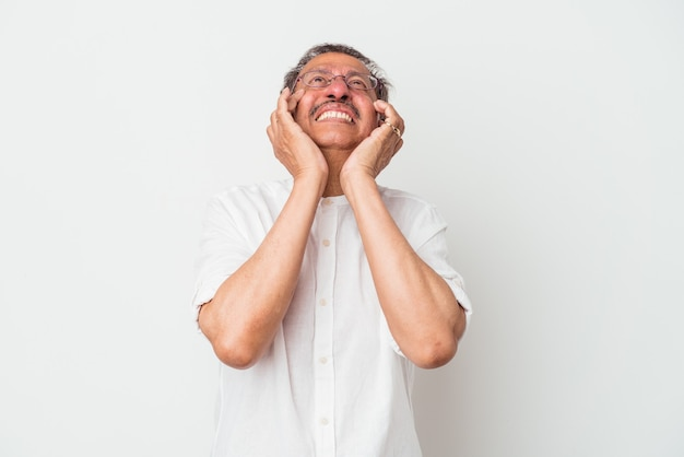 Middle aged indian man isolated on white background whining and crying disconsolately.