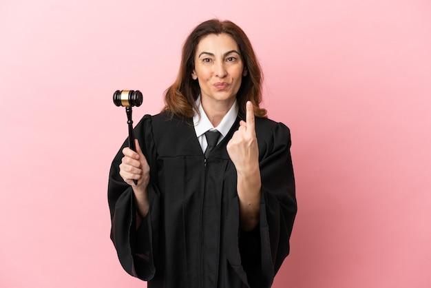 来るジェスチャーをしているピンクの背景に分離された中年裁判官の女性