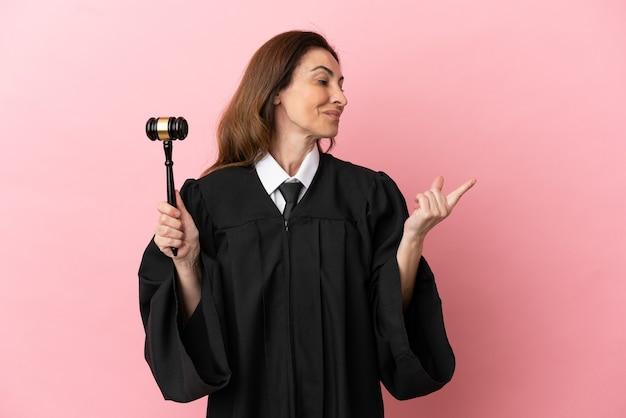 指を持ち上げながら解決策を実現しようとピンクの背景に分離された中年裁判官の女性