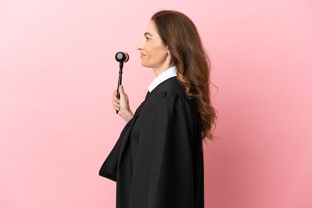 横向きの位置で笑ってピンクの背景に分離された中年裁判官の女性