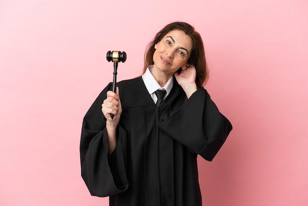 笑ってピンクの背景に分離された中年裁判官の女性