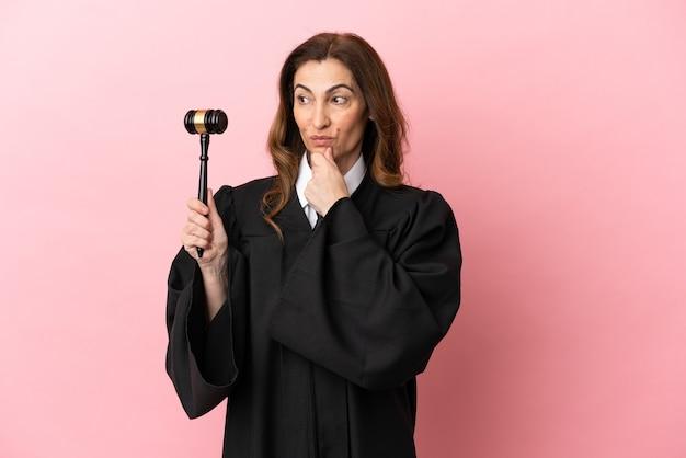横を見て笑っているピンクの背景に分離された中年裁判官の女性