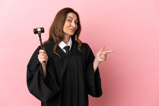 横に指を指しているピンクの背景に分離された中年裁判官の女性