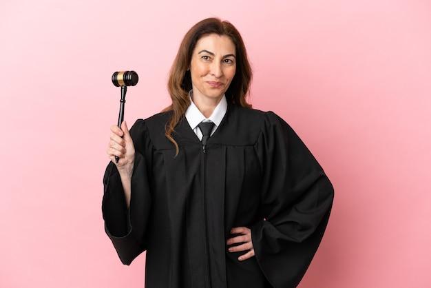 ピンクの背景に分離された中年裁判官の女性は、腰に腕と笑顔でポーズをとる