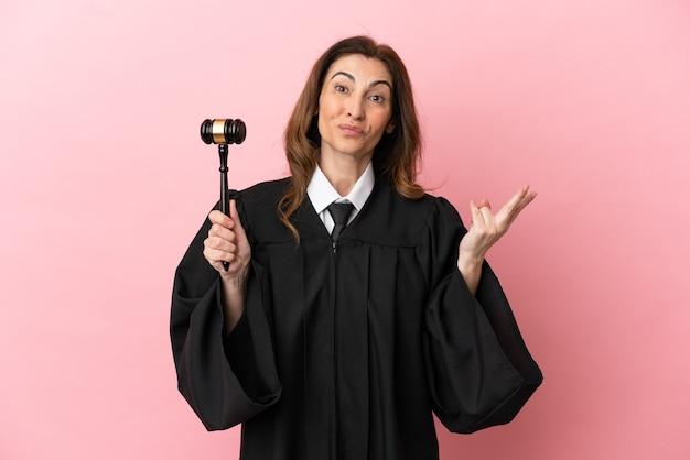 笑顔と勝利のサインを示すピンクの背景に分離された中年裁判官の女性