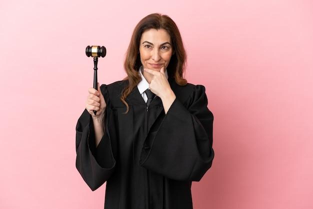 ピンクの背景思考に分離された中年裁判官の女性