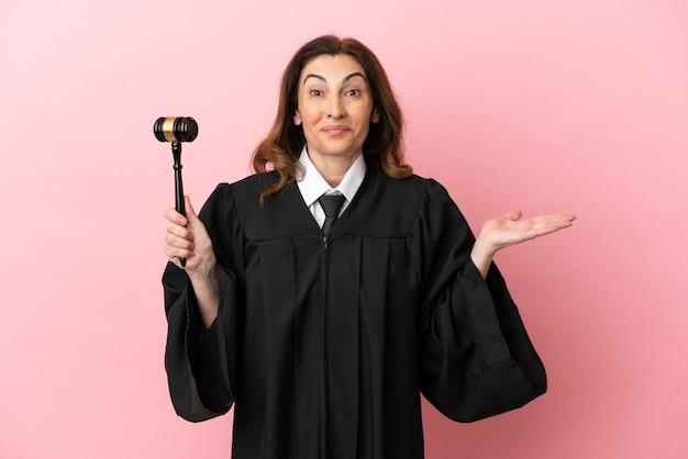 ショックを受けた表情でピンクの背景に分離された中年裁判官の女性