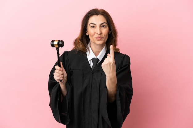 Middle aged judge woman isolated on pink background doing coming gesture
