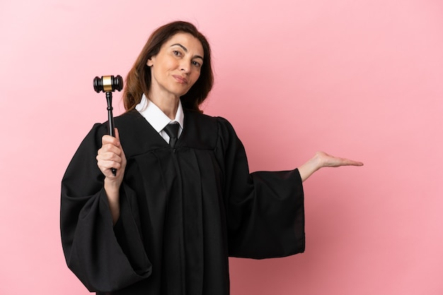 Middle aged judge woman isolated on pink background extending hands to the side for inviting to come