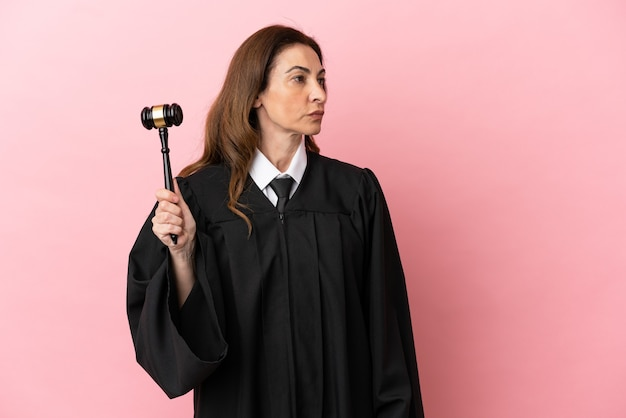 Middle aged judge woman isolated on pink background looking to the side
