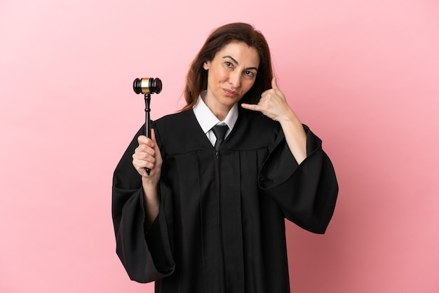 Middle aged judge woman isolated on pink background making phone gesture. call me back sign