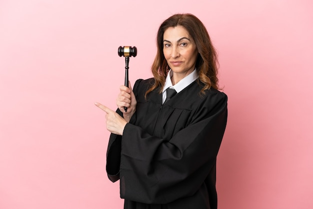 Middle aged judge woman isolated on pink background pointing back