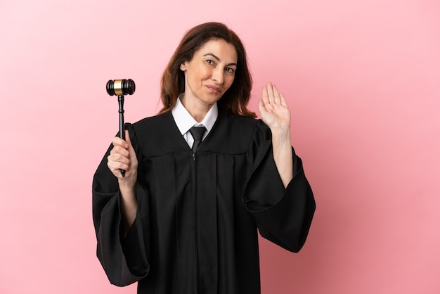 Middle aged judge woman isolated on pink background saluting with hand with happy expression