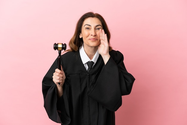 Middle aged judge woman isolated on pink background shouting with mouth wide open