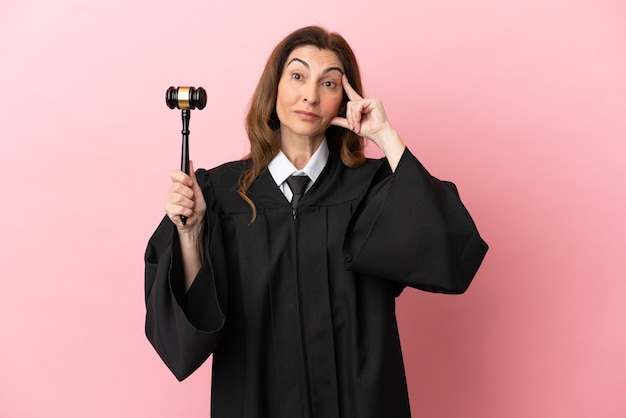 Middle aged judge woman isolated on pink background thinking an idea