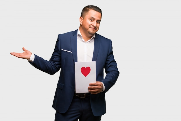 Middle aged latin man celebrating valentines day confused and doubtful