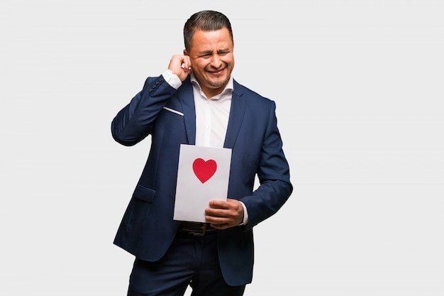 Middle aged latin man celebrating valentines day covering ears with hands